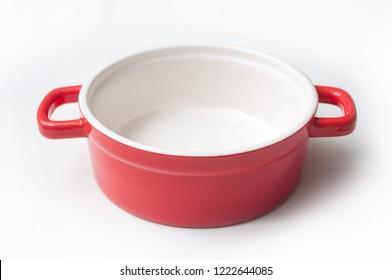 closeup of red ceramic saucepan on white background