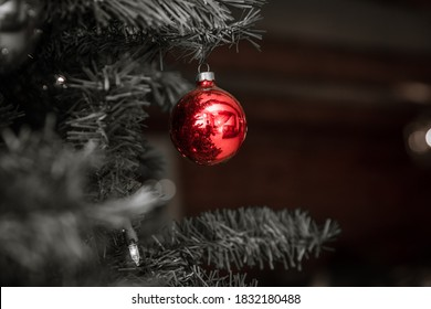 Closeup of red Christmas ornament in otherwise black and white photo.