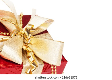 closeup of a red christmas present with golden ribbons on white background