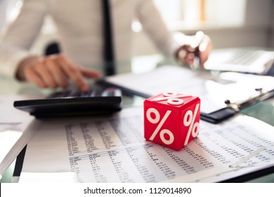 Close-up Of Red Cubic Block With Percentage Symbol In Front Of Businessperson Calculating Invoice