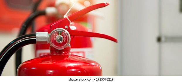Close-up the red fire extinguishers tank at the door exit way in the building concepts of prevent case for emergency and safety rescue and fire training. - Shutterstock ID 1925378219