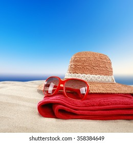 closeup of red glasses on red towel and hat and background of beach with sea