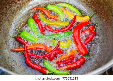 Closeup of red and green chilies frying in oil
