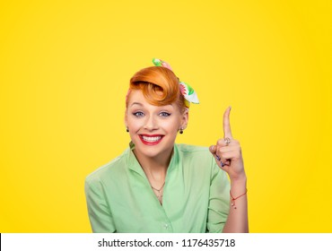 Closeup red head young woman pretty pinup girl green button shirt pointing finger up has a brilliant idea sign gesture looking at you camera isolated yellow background retro vintage 50's style.