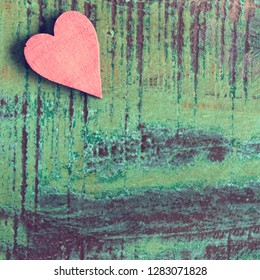 Closeup of a red heart on a green wooden table