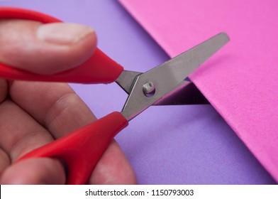 closeup of red scissors in hand cutting colored paper