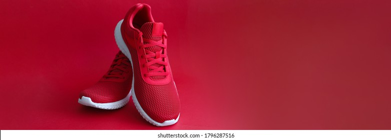 Close-up of red sneakers on bright backdrop. Sport footwear for running and fitness. Amazing pair of shoes. Active lifestyle. Nice texture with white sole and laces
