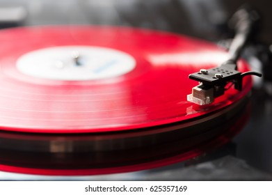 Close-up of red spinning vinyl with copy space. Analog Vinyl record player.