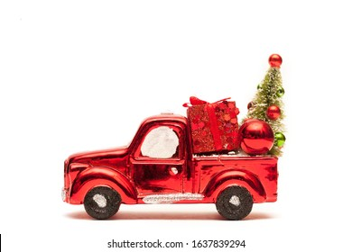 Close-up of red toy truck with Christmas presents on white background. Gift box, bauble, Christmas tree. Christmas delivery, New Year presents, children party