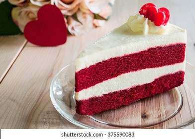 Closeup Red Velvet Cake with glass plate on wooden. Red heart and bouquet of roses background. Suitable for valentine occasion.