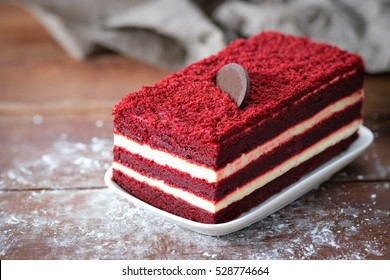 Close-up red velvet cake and white cream on wooden table with space to write. Select a focus.
