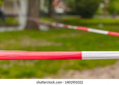 Closeup of red and white tape setting up a perimeter, a grass field that should not be walked on.