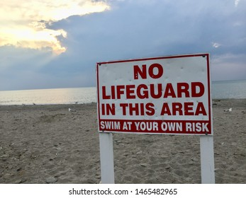 Closeup of red and white wooden warning sign that states no lifeguard in this area swim at your own risk off centered with sun peaking through the clouds with beach water and sand background