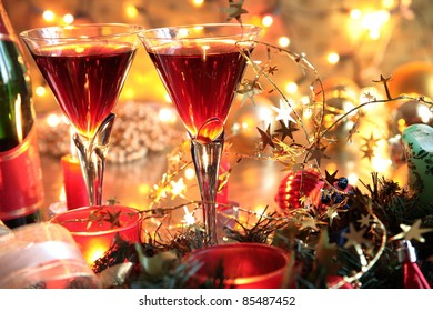 Closeup of red wine in glasses, bottle and candle lights on golden background with twinkle lights.