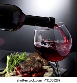 Closeup of red wine pouring into glass with meat and cheese