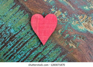Closeup of a red wooden heart on a table