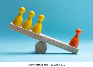 Close-up Of Red And Yellow Pawns Figures Balancing On Wooden Seesaw Over Blue Surface