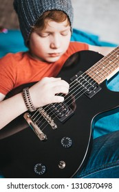 Closeup of a red-haired stylish boy playing blues rock on a black electric guitar