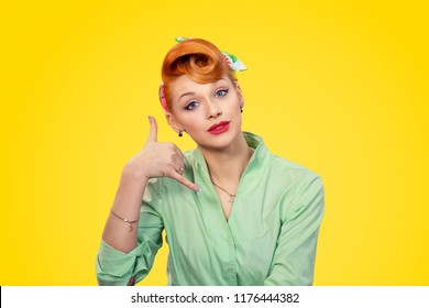 Closeup redhead young woman pretty pinup girl retro vintage 50's style green button shirt making showing call me sign gesture asking to contact her looking at you camera isolated yellow background.