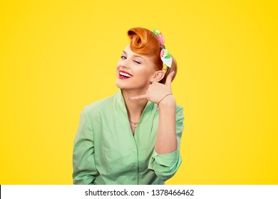 Closeup redhead young woman pretty pinup girl retro vintage 50's style green button shirt winking eye making showing call me sign gesture asking to contact her looking at camera over yellow background