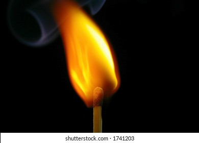 Closeup of a red-tipped wooden match stick at ignition.  Red, orange, and yellow flame.  Black background.
