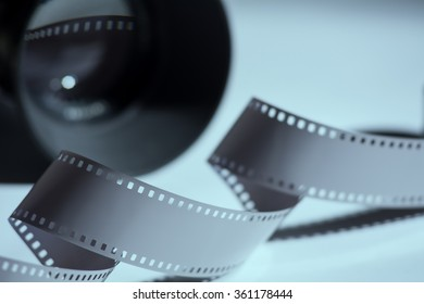 Close-up reel of film and spun in the background camera lens.