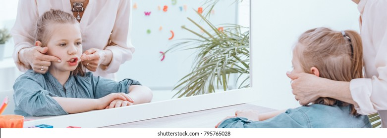 Close-up of reflection in the mirror of young girl exercising pronunciation with speech therapist
