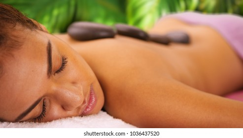 Close-up of relaxed black woman laying down with hot stones on her back