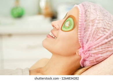 Closeup of relaxed female client in disposable hat and with cucumber mask on eyes lying on couch in beauty salon. Young woman caring about skin and doing rejuvenation procedure in spa.