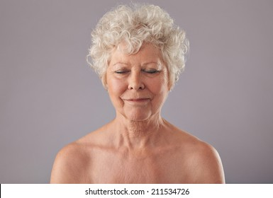 Close-up of relaxed old woman on grey background with her eyes closed in thought. Naked senior female against grey background.