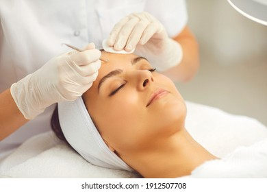 Close-up of relaxed womans face getting facial pores cleaning with special metal vidale needle from blackheads and acne from cosmetologist in beauty salon. Professional cleaning for skin concept