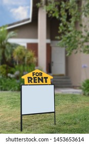 Closeup of a For Rent sign in front of a home. The house is out of focus, in vertical format.