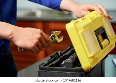 Close-up of repairman opens toolbox and puts his tools in it after his work