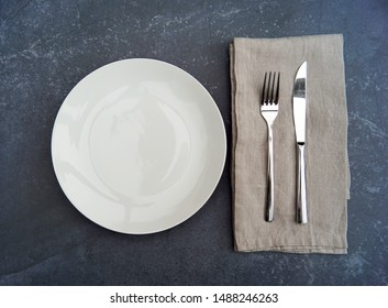 closeup of a restaurant bistro dining cafe serving of a white empty porcelain plate with silverware knife and fork on a natural brown beige linen cloth napkin on black table