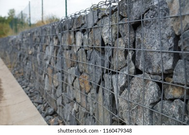 Close-up of a retaining wall made of stones. A wall called a gabion.
