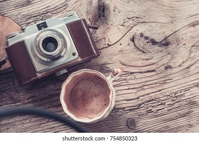 Closeup of retro camera and cup of coffee