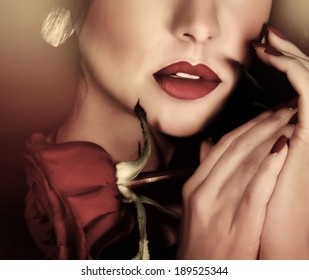 Closeup retro style photo of beautiful woman, half of face, sexy red lips and red rose in hands, passion and sensuality concept