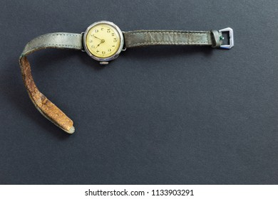 Closeup of a retro style yellow colored wristwatch with worn leather straps on black background.