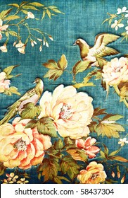 Closeup of retro tapestry fabric pattern with classical image of the colorful  flowers and birds on blue background.