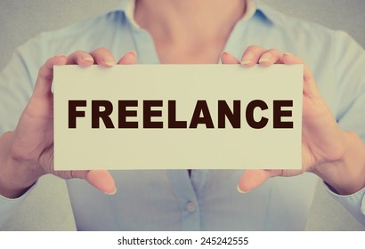 Closeup retro vintage style image businesswoman, female, girl, person hands holding white rectangle sign or card with message freelance isolated on gray office wall background. Self-employed concept.