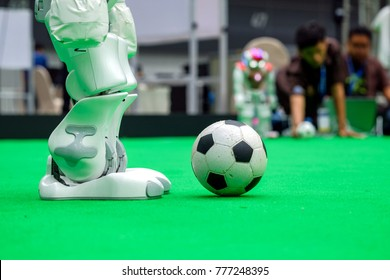 Close-up right legs of soccer robot to playing football in the match on artificial soccer arena, people on blurred background
