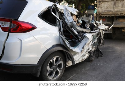 Closeup of right side of damaged smashed white sedan car from road traffic accident. The image for road traffic accident reduction campaign and  insurance business.