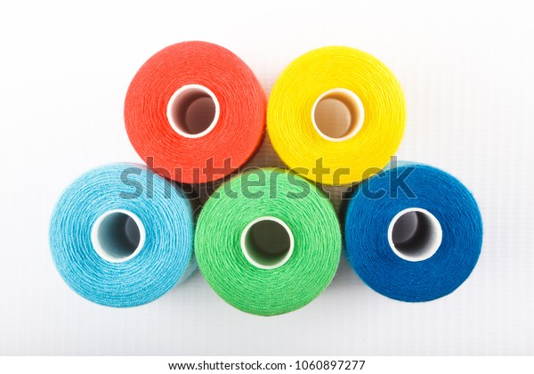 Close-up rings of red, yellow, blue and green thread spools