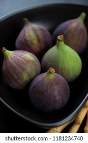 Close-up of ripe figs in a black bowl, selective focus, vertical shot