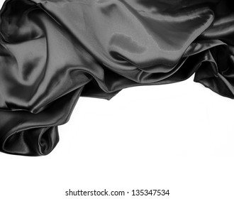 Closeup of rippled black silk fabric on plain background