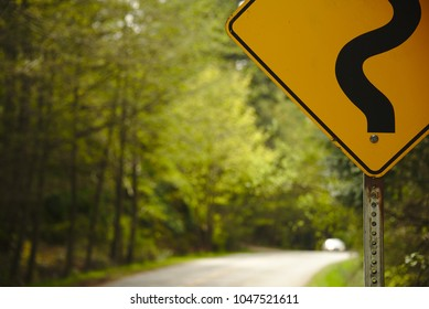 Closeup of a road sign with a nice blurry background of trees and a road