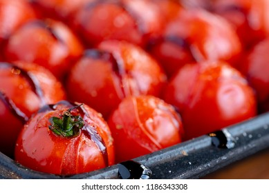 closeup of roasted cherry tomatoes in a black metal baking dish. The cherry tomatoes are roasted with extra virgin olive oil and balsamic vinegar