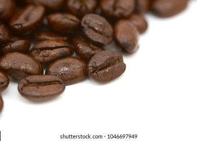 Close-up of roasted coffee beans in selective focus, on a white background