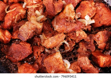 Close-up of roasted meat slices with sliced onion and red sauce on the frying pan
