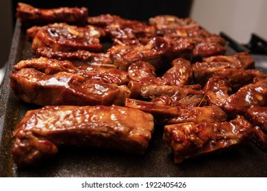 closeup of roasted pork ribs with barbecue sauce and caramelized with honey. Tasty homemade snack or small business ow